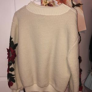 White fluffy sweatshirt, red roses on the sleeves